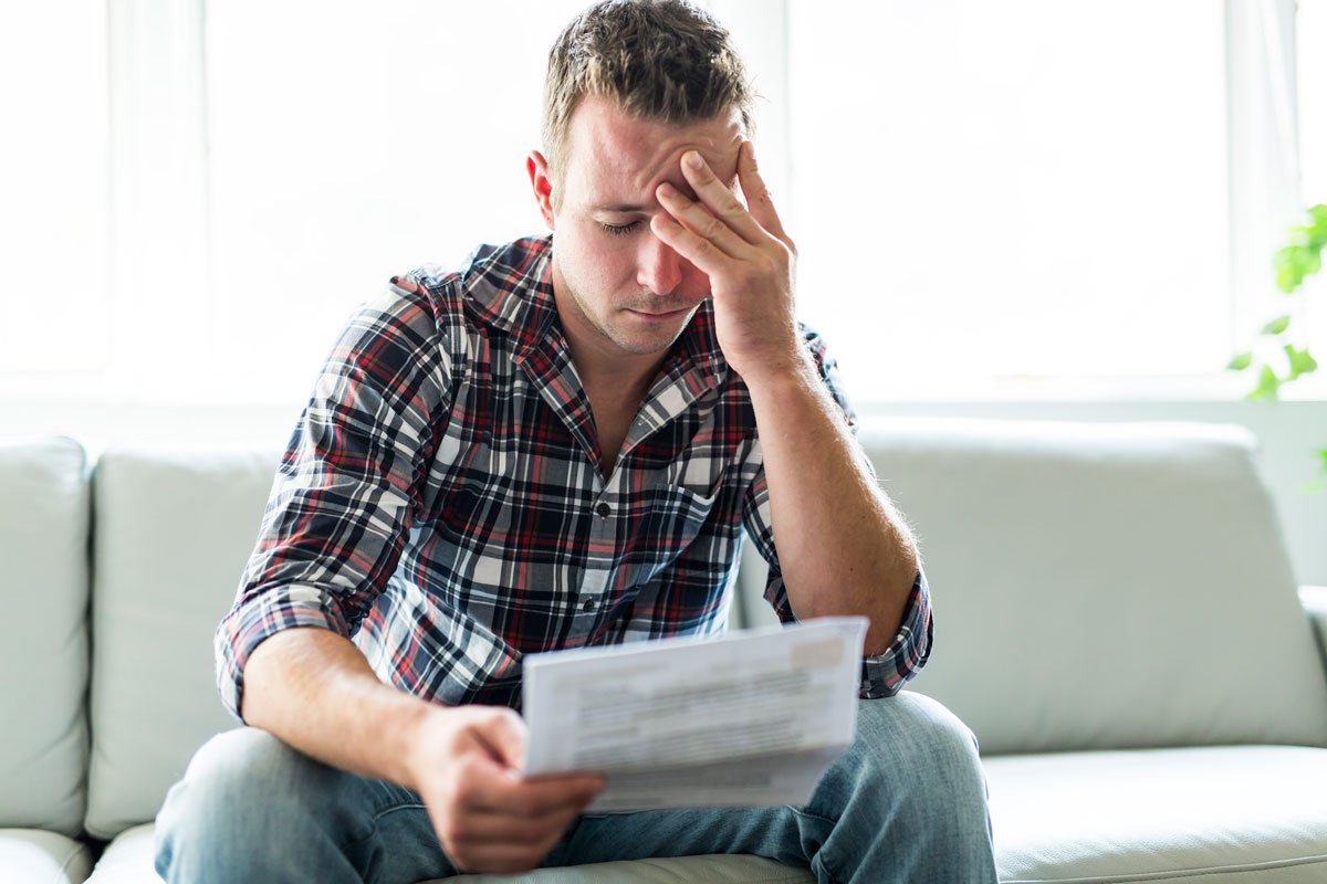photo of a man reviewing his credit report showing how bad his credit situation is and the challenges he will face when applying for a mortgage