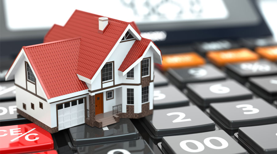 photo of a calculator holding up a house, showing the importance of planning your mortgage financing with a mortgage professional such as Advantage Mortgage