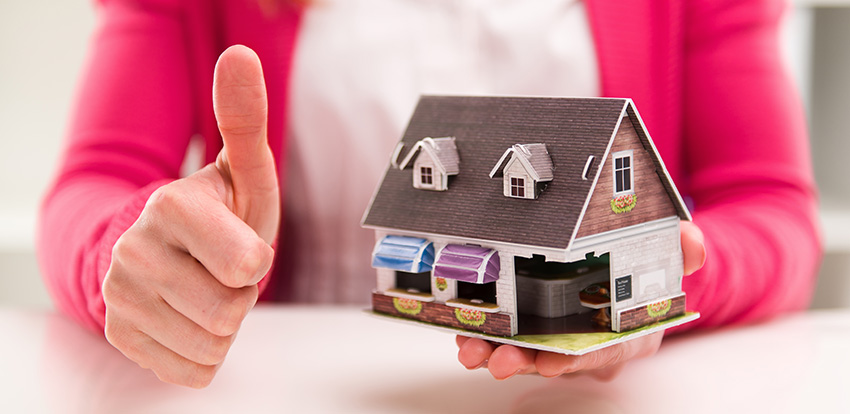 photo of a mortgage broker holding up a small model home and giving a thumbs up, showing that it helps to hire a mortgage broker to get approved for a home loan